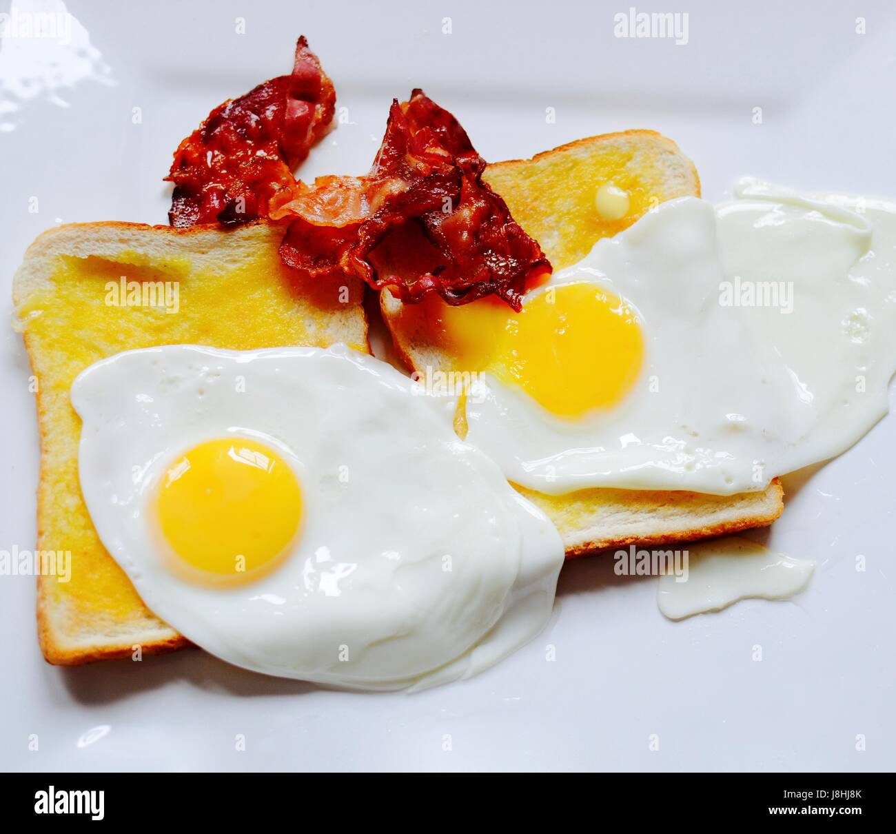 Bacon and fried eggs on white toast - Stock Image