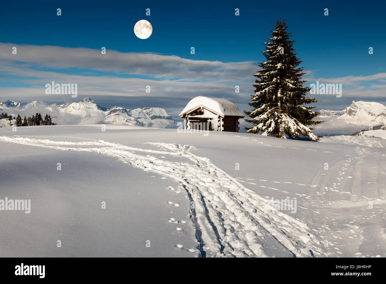Full Moon above Small Hut and Fir Tree on the Top of the Mountain in Megeve, French Alps - Stock Image