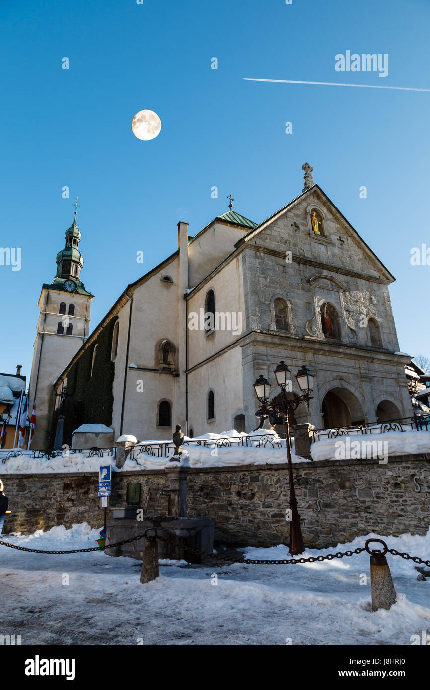 Full Moon above Medieval Church on the Central Square of Megeve, French Alps - Stock Image