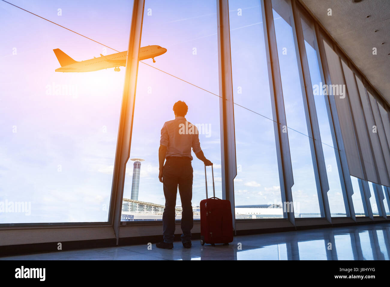 Businessman with suitcase at airport international departure gate looking at flying airplane through the windows - Stock Image