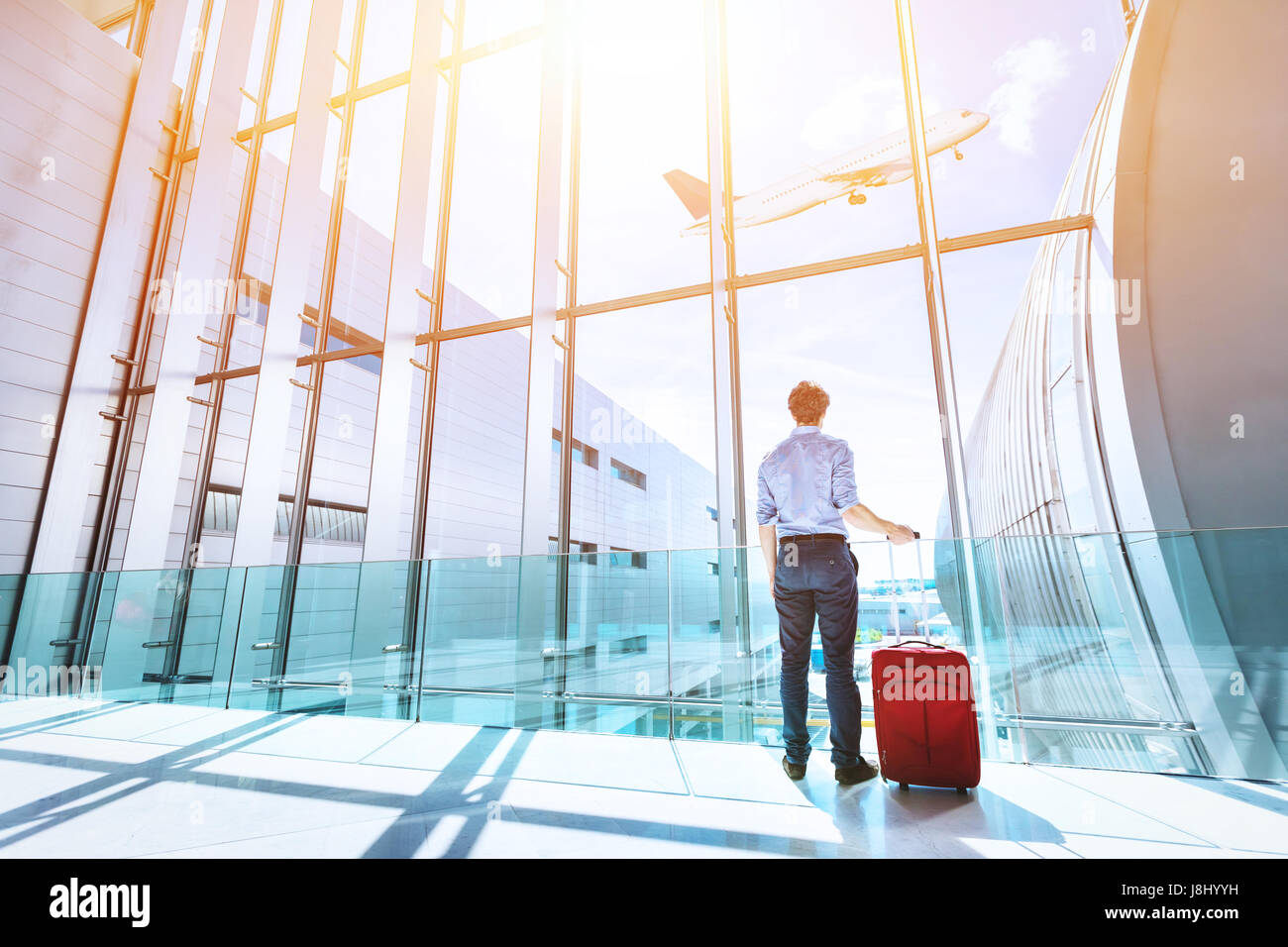 Businessman at airport terminal boarding gate looking at airplane flying through the window - Stock Image