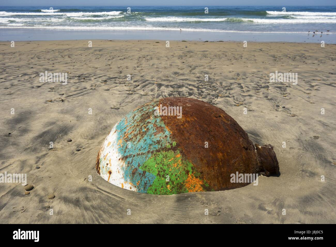 Old Rusted Sea Buoy Washed out by High Tide of Pacific Ocean on Torrey Pines State Beach north of La Jolla Shores - Stock Image