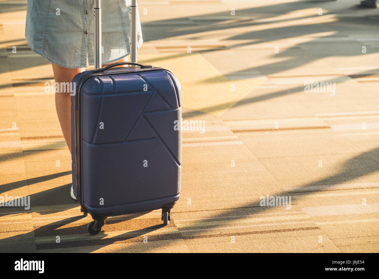 Young casual woman wear white sneakers standing with travel suitcase with morning sunlight through window at airport - Stock Image