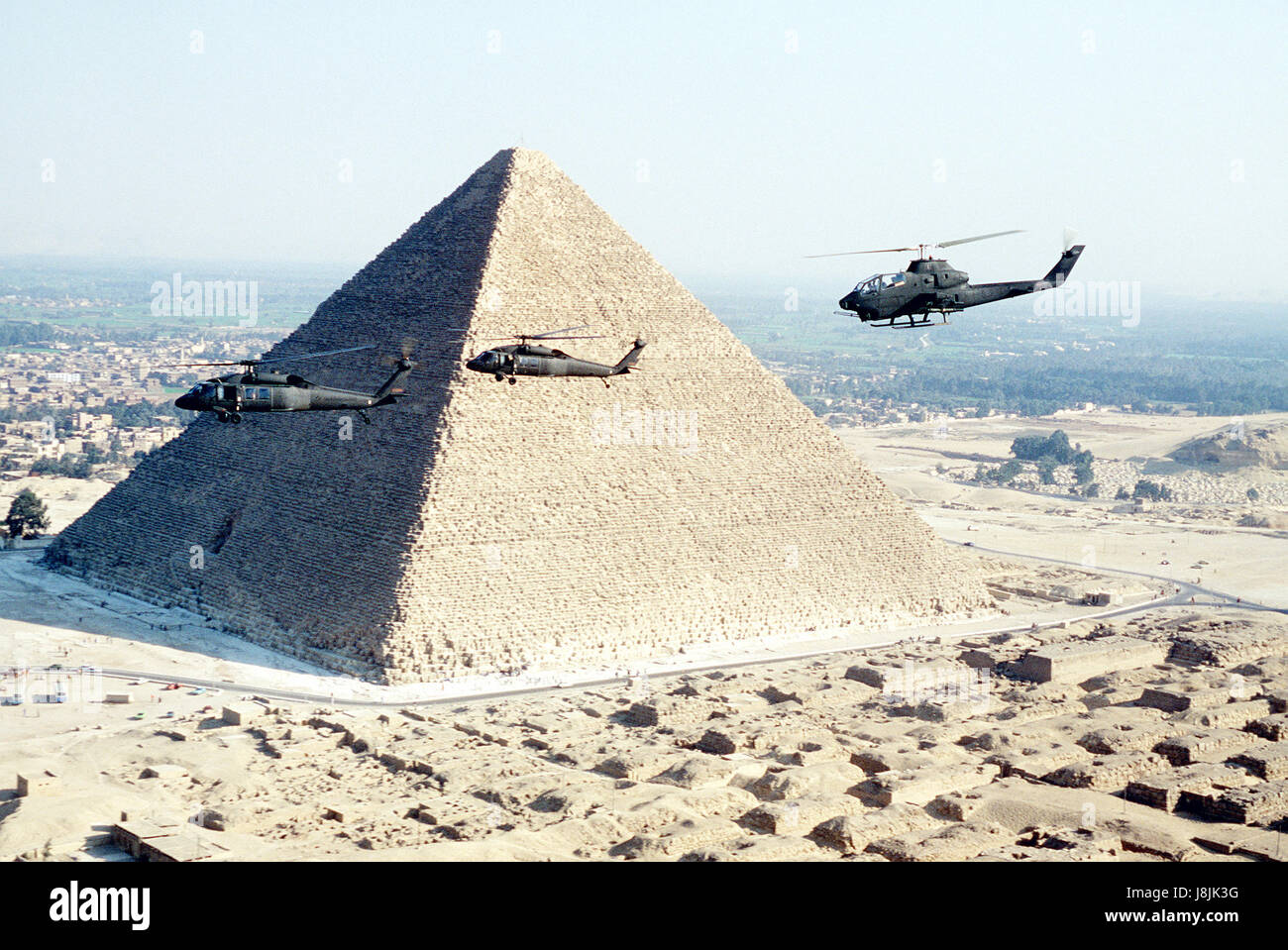 Military helicopters flying in front of a pyramid in Egypt - Stock Image