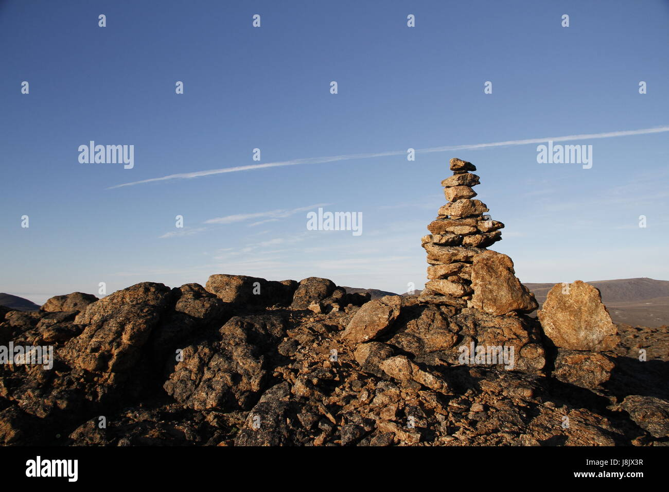 Inukshuk or Inuksuk at the top of the mountain along a hiking trail near the community of Qikiqtarjuaq, Broughton - Stock Image