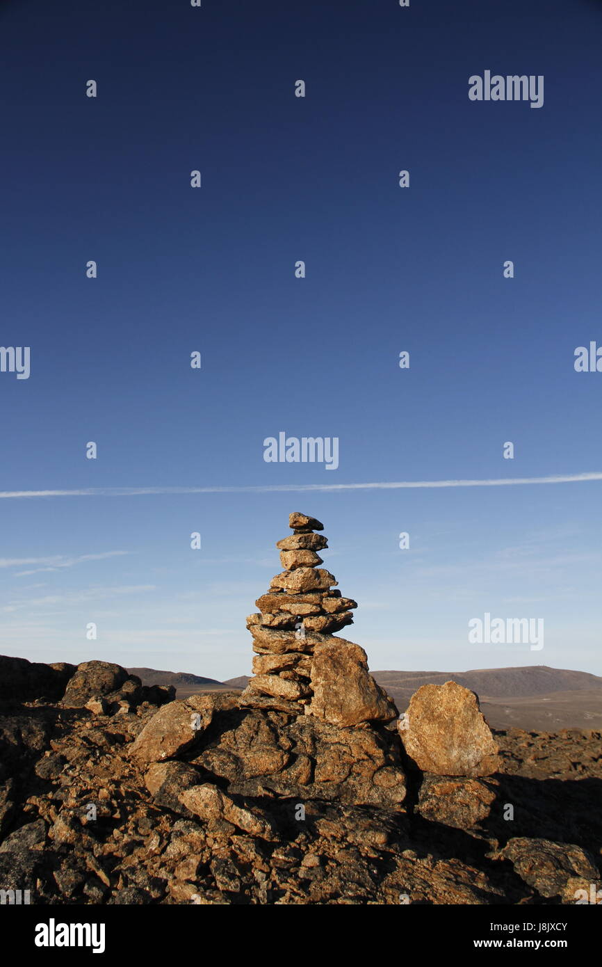 Inukshuk or Inuksuk at the top of the mountain along a hiking trail near the community of Qikiqtarjuaq, Broughton Stock Photo