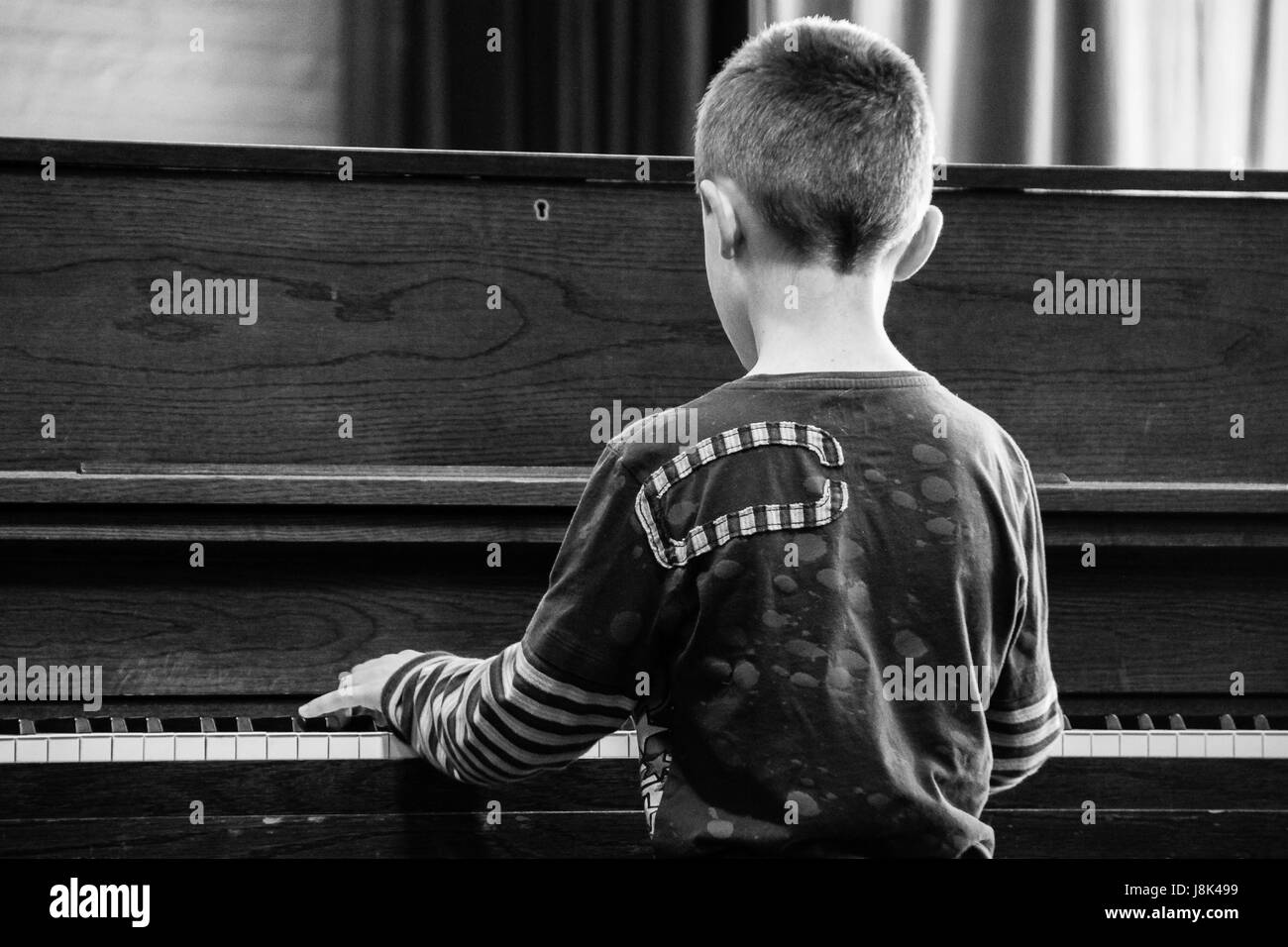 Young boy performs in a studio at an upright piano during a music recital. - Stock Image