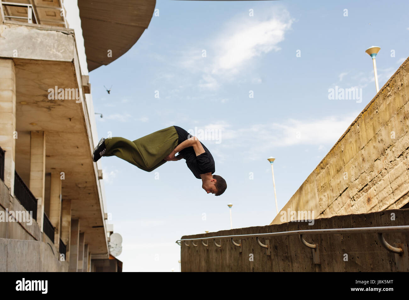 Young man back flip. Parkour in the urban space. Sport in the city. Sport Activities outdoors. - Stock Image