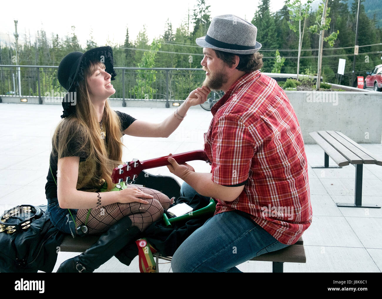 Street musicians sing a duet in front of a shopping centre.  Whistler BC, Canada - Stock Image