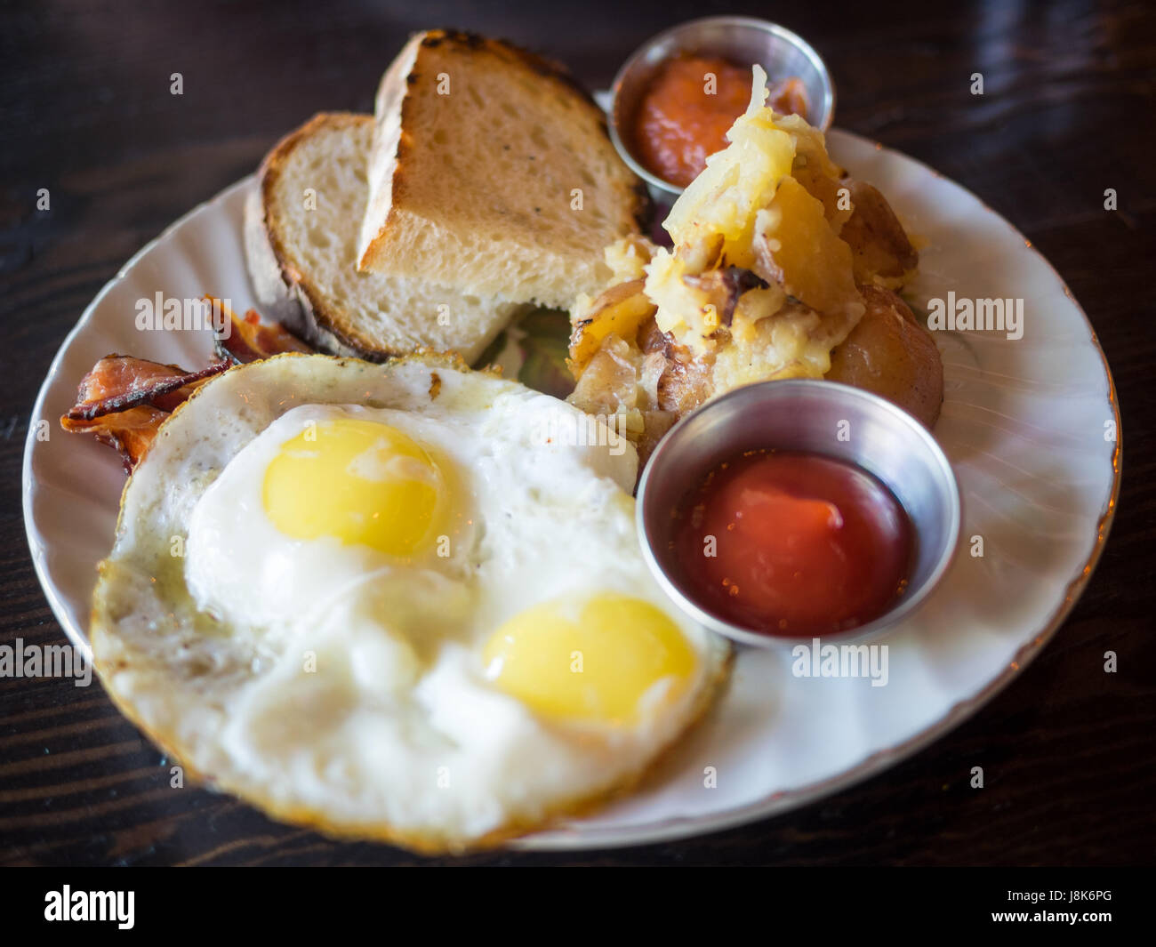 Two sunny side up eggs, hash brown potatoes, sourdough toast, and bacon (Canadian breakfast) from Chartier Restaurant - Stock Image