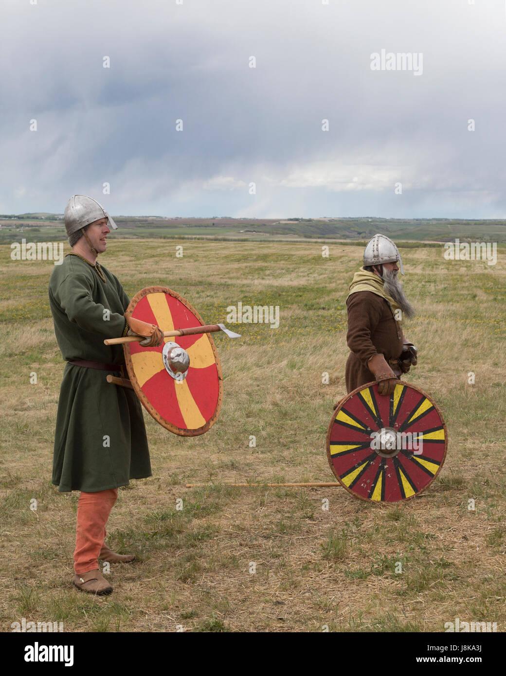 Men wearing traditional Viking warrior costumes during battle reenactment - Stock Image