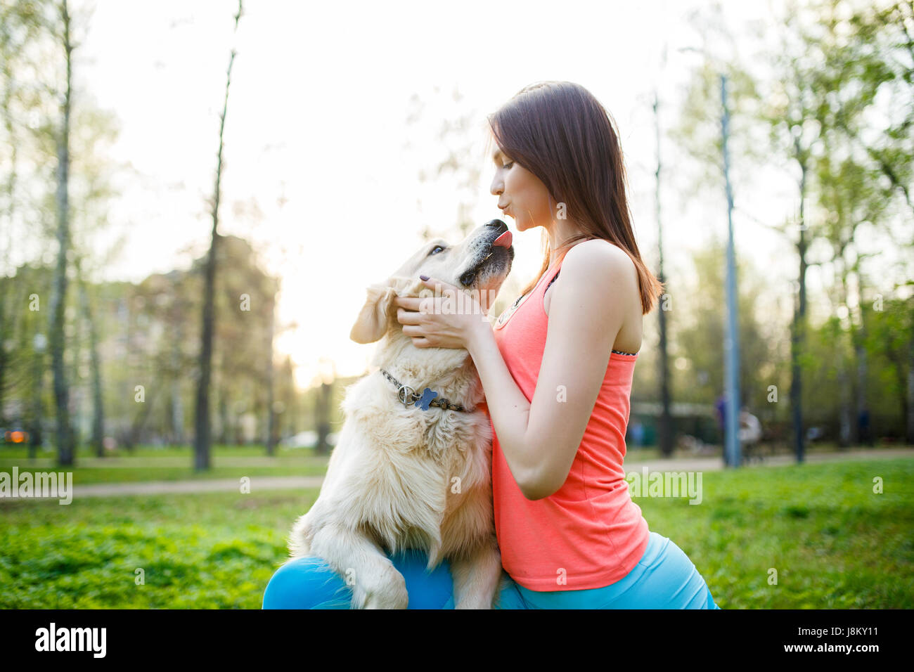 Woman hugging dog on lawn - Stock Image