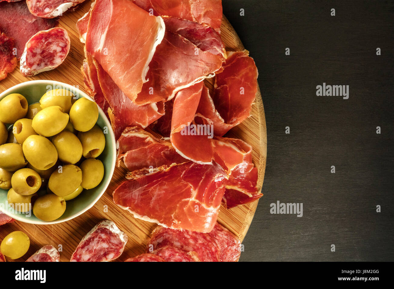 An overhead photo of a Spanish cold meats platter with jamon and payes sausage, with green olives, on a dark background - Stock Image