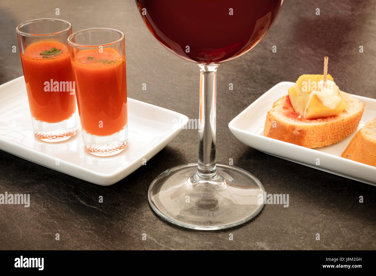 Spanish tapas in a modern bar. A glass of red wine, two shots of gazpacho, cold tomato soup, and pinchos of tortilla, - Stock Image