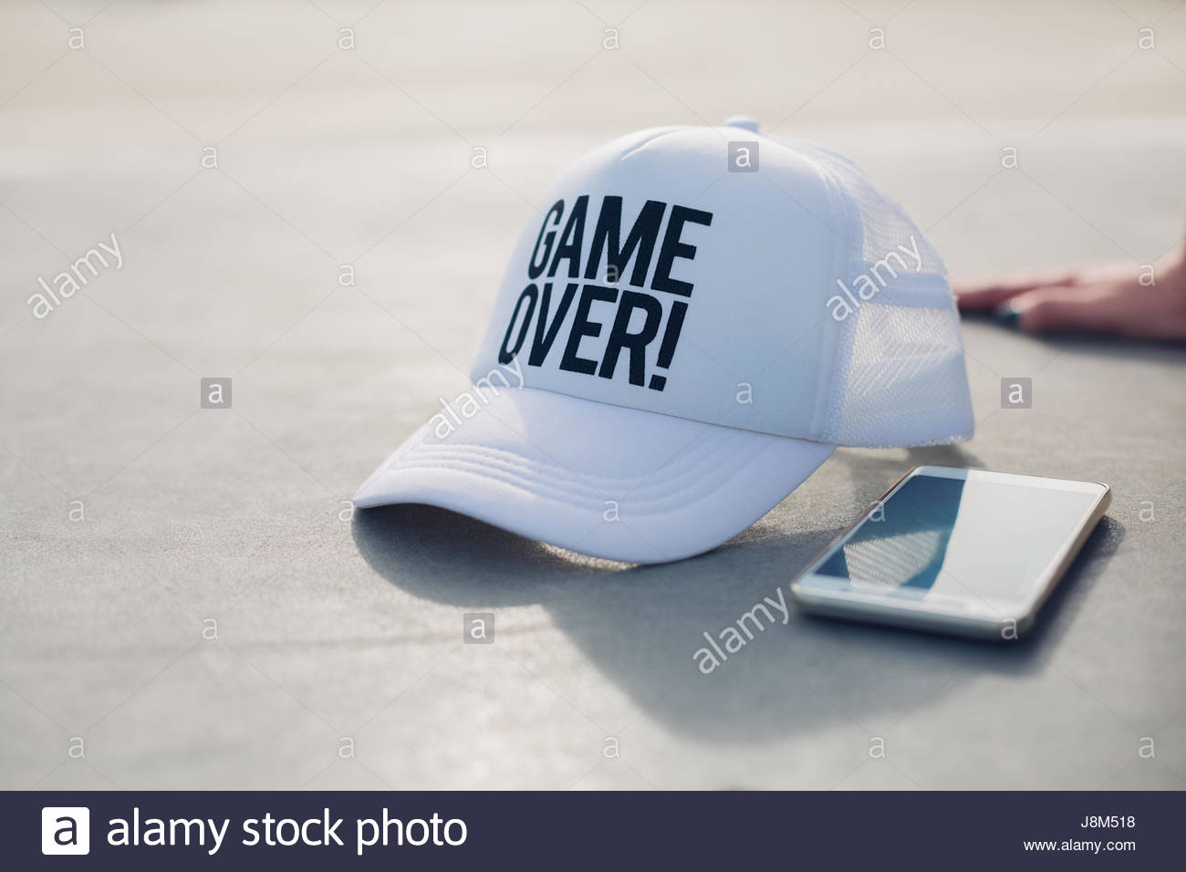 Sports equipment, game over cap and mobile phone - Stock Image