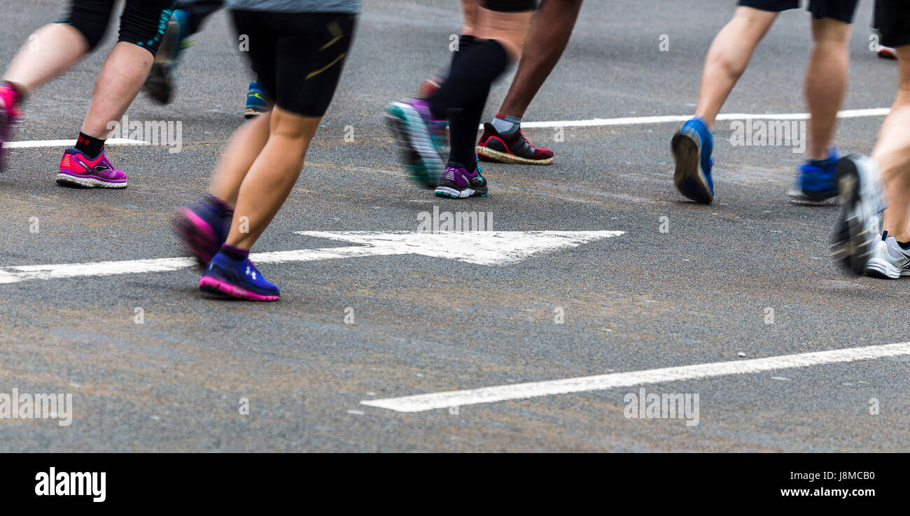 A slow shutter speed has been used to blur the motion of the feet of marathon runners jogging over a white arrow - Stock Image