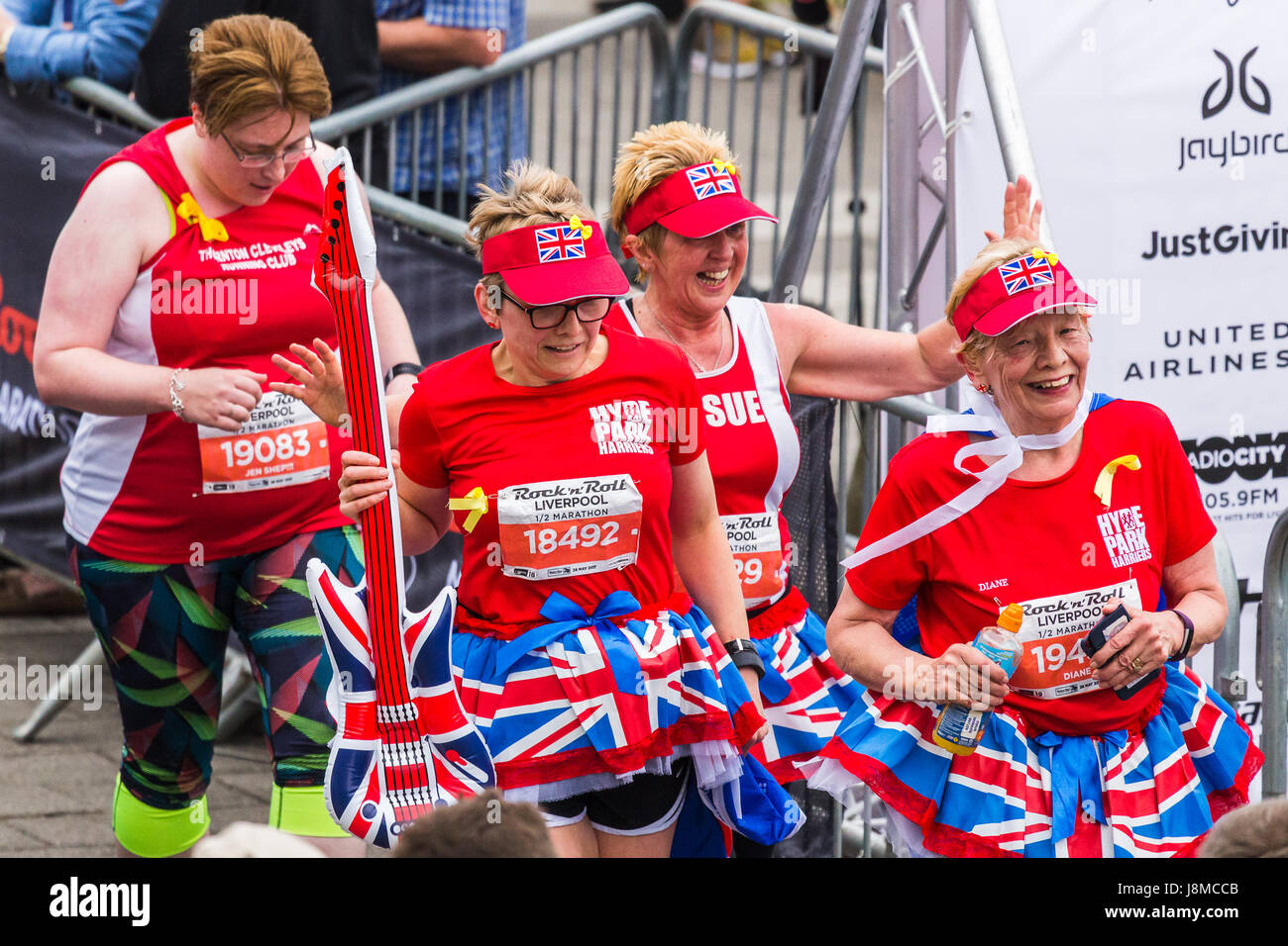 Mature adults from Hyde Park Harriers cross the finishing line in the 2017 Liverpool Rock n Roll half marathon on - Stock Image
