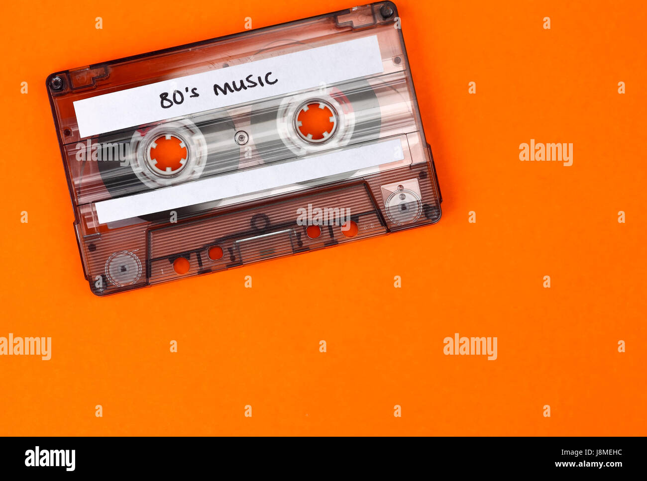 Retro cassette tape which has the wording 80's music wrote on it and an orange background - Stock Image