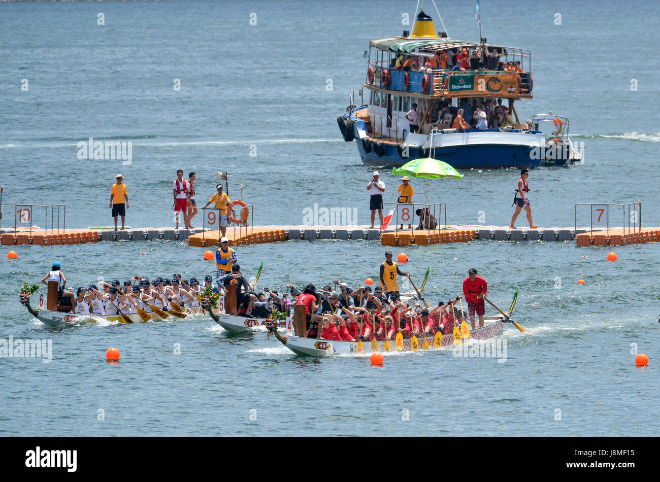 A spectator boat lines up by the race start line.Annual International Dragon Boat races at Stanley Beach, Hong Kong - Stock Image