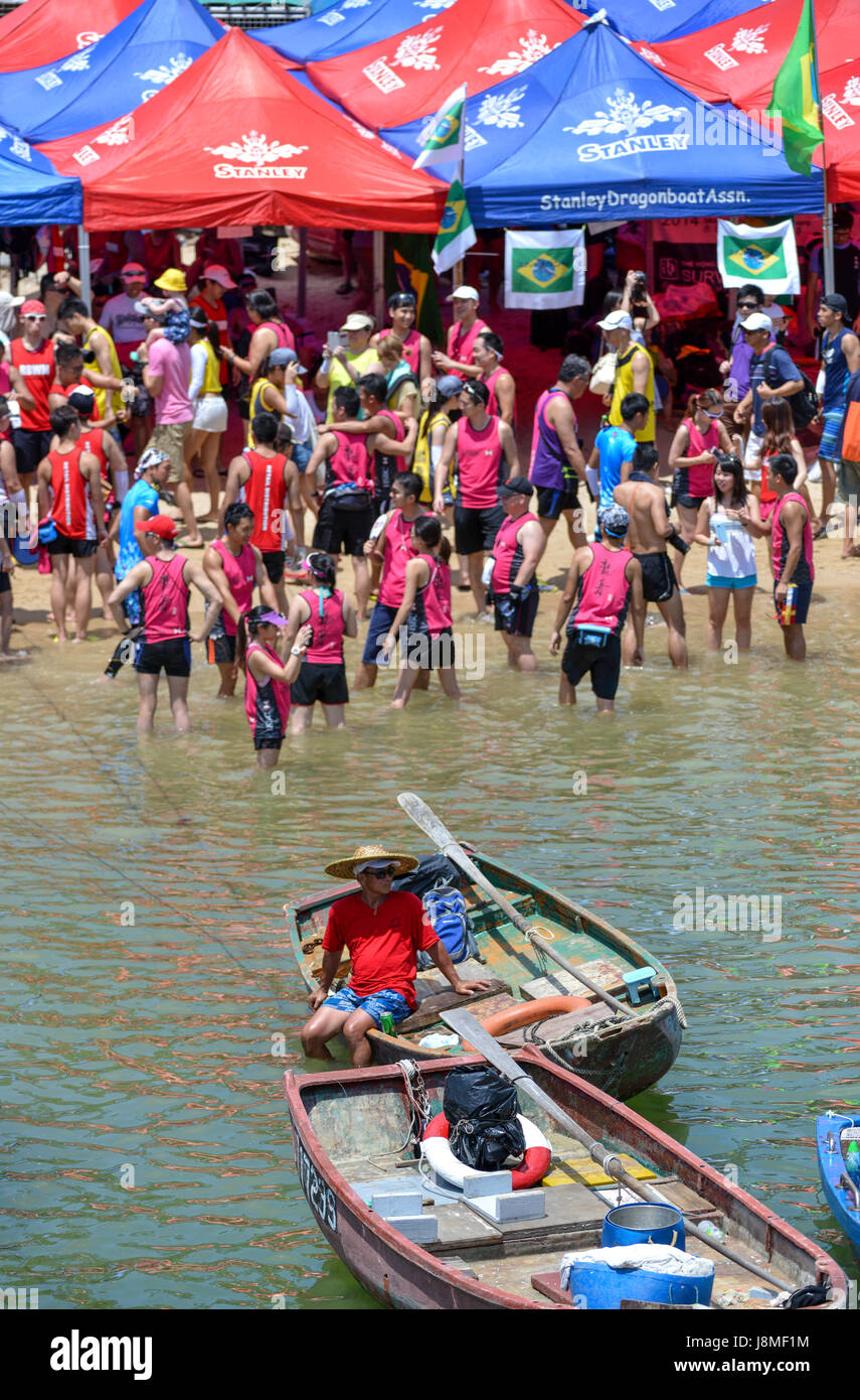Crowds and dragon boat teams gather on the beach while locals sit in fishing boats to watch.Annual International - Stock Image