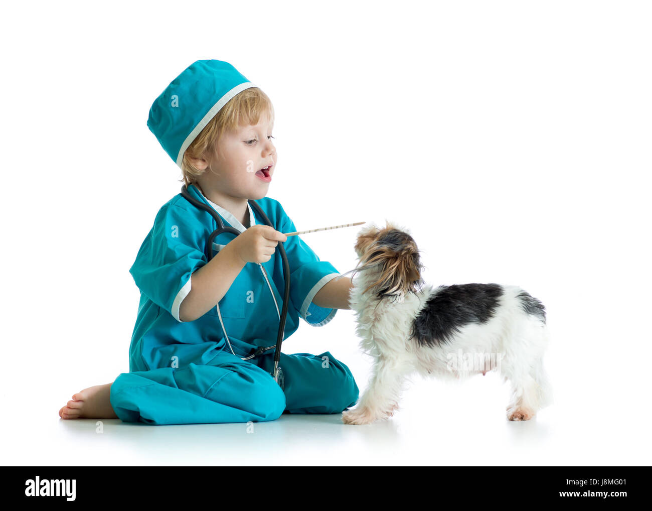 Child weared doctor clothes playing veterinarian with dog - Stock Image