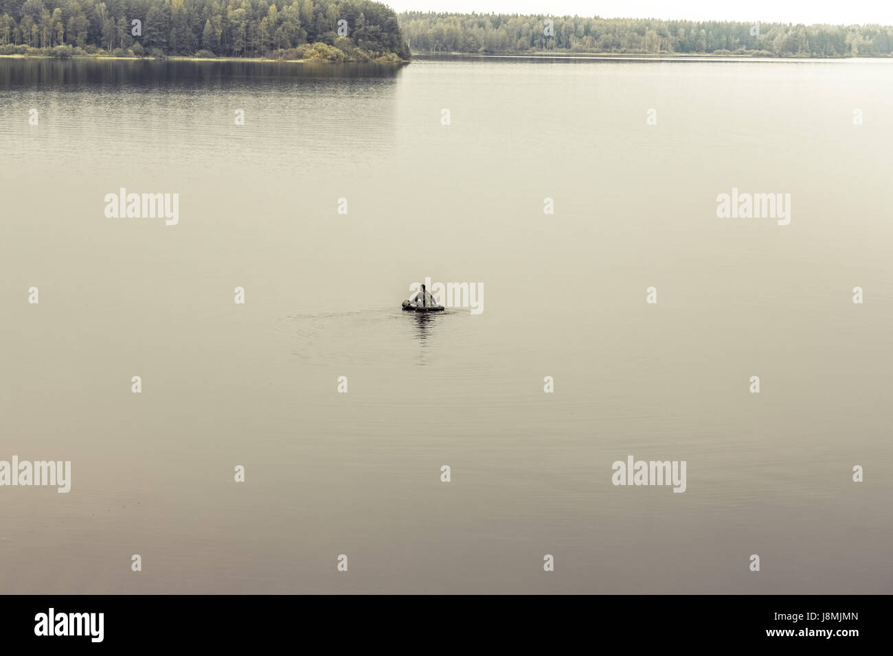 Exploring man in boat in the middle of vast expanses of tranquil lake. Symbolizing loneliness and searching - Stock Image