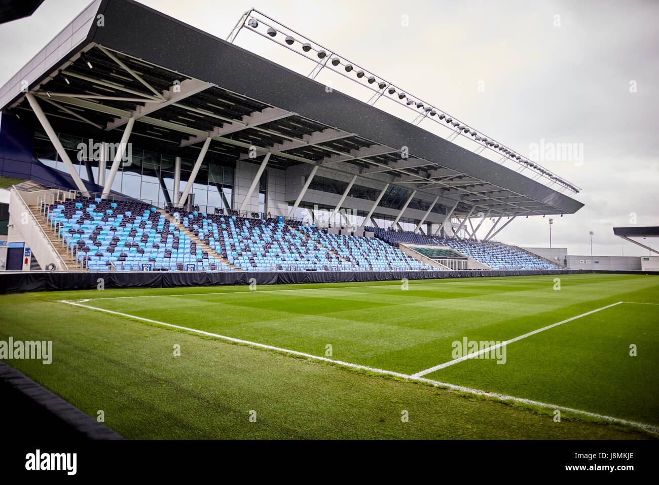 Manchester City Etihad Stadium academy stadium, the mixed shades of blue seats help make the empty stadium look - Stock Image