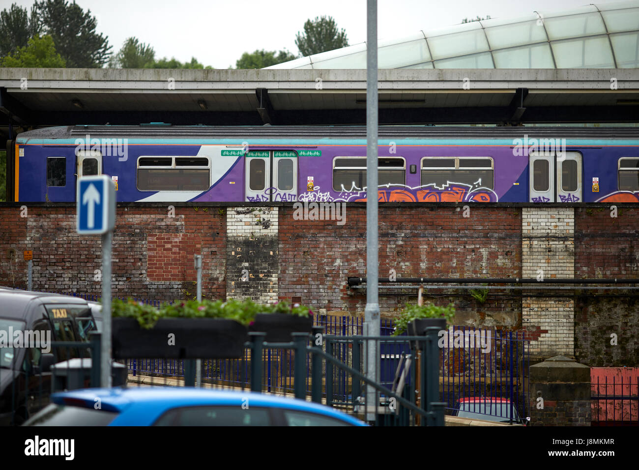 Blackburn railway station, a local Northern Sprinter train covered in Graffiti stopped in the platform. - Stock Image