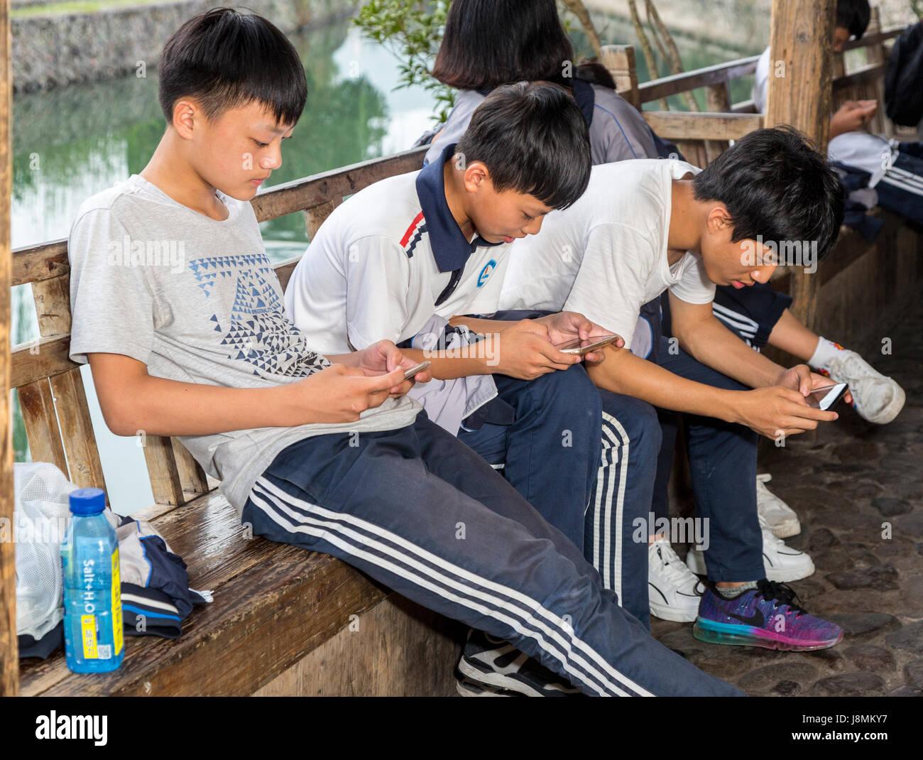 Yantou, Yongjia, Zhejiang, China.  Teenage Boys on Lishui Street Examining Their Cell Phones. - Stock Image