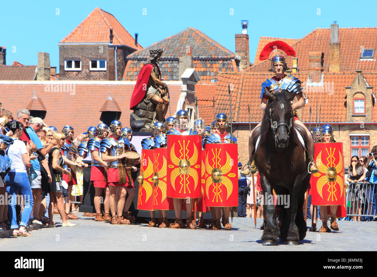 Roman Legionaries pulling a wooden statue of Jesus Christ during the Procession of the Holy Blood in Bruges, Belgium - Stock Image