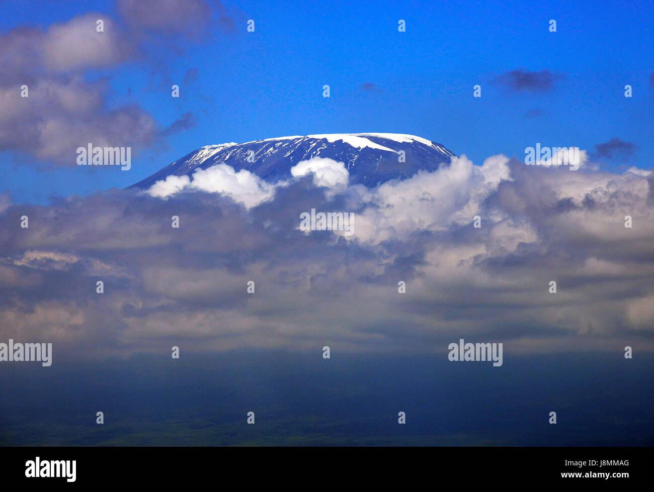 Mount Kilimanjaro peeking out of the clouds. - Stock Image