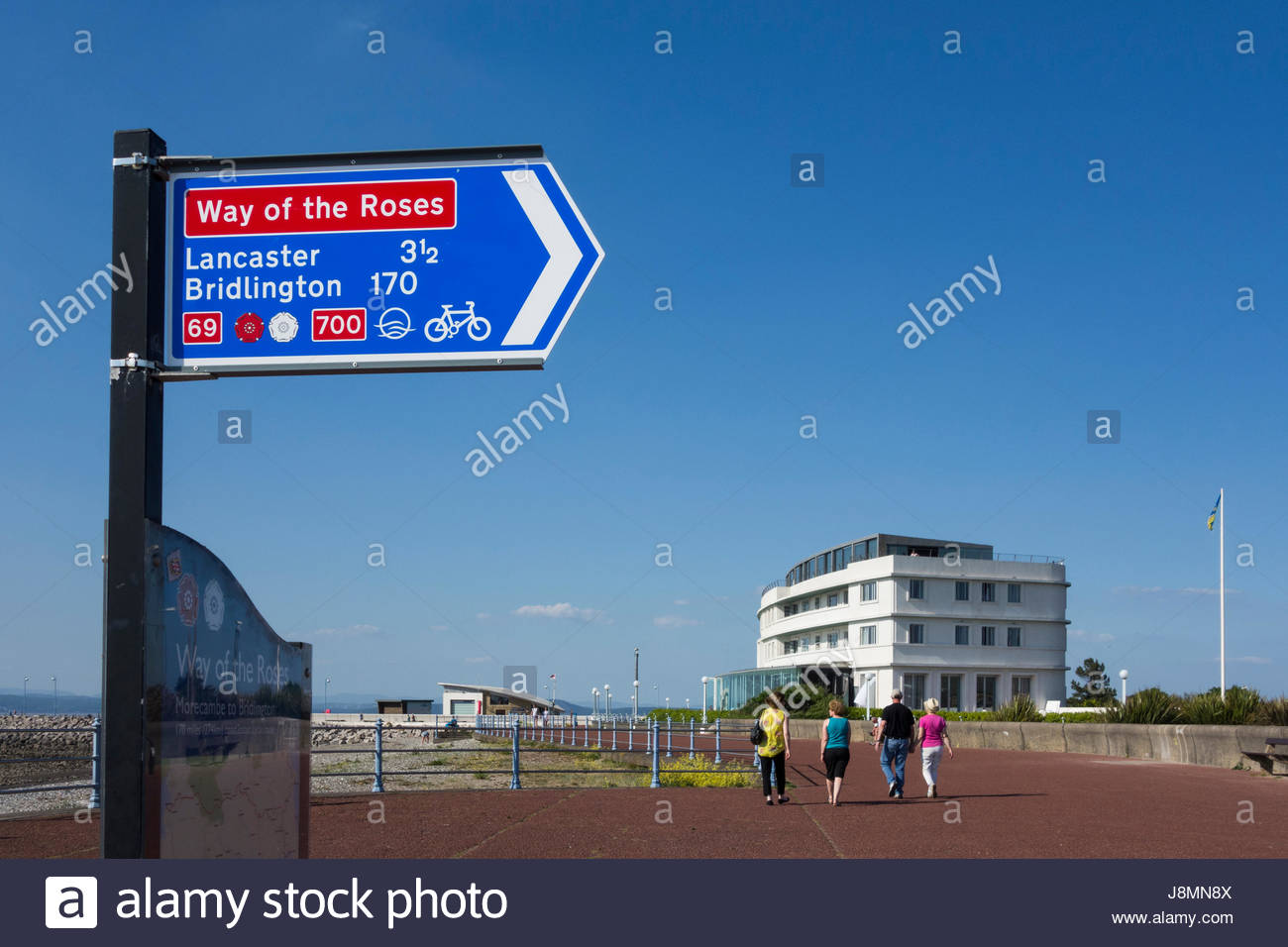 Sign for the start of the Way of the Roses Cycle Route on Morecambe promenade with the famous Midland Hotel in the - Stock Image