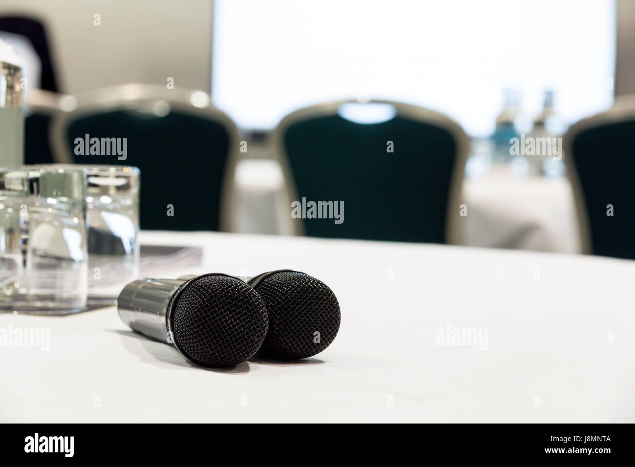 Two microphones on a white table used for Q&A at a conference or meeting venue. Chairs and a screen in the background - Stock Image