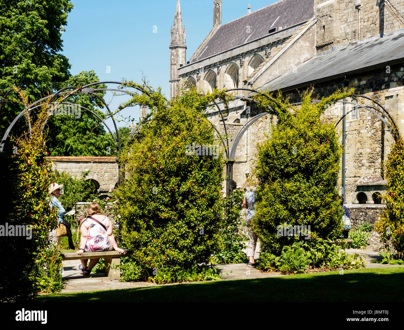 Visitors relaxing in the Dean Garnier Garden off the Inner Close of Winchester Cathedral in Hampshire, England. Stock Photo