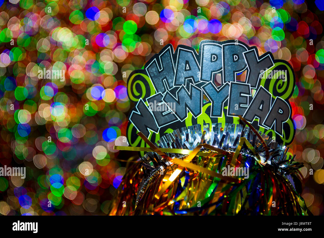 Happy New Year party hat sparkling against a glowing holiday celebration background in a colorful night view - Stock Image