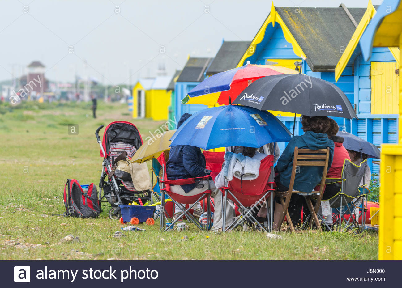 People take shelter under umbrellas in wet weather on a miserable Bank Holiday Monday on 29th May 2017 in Littlehampton, - Stock Image