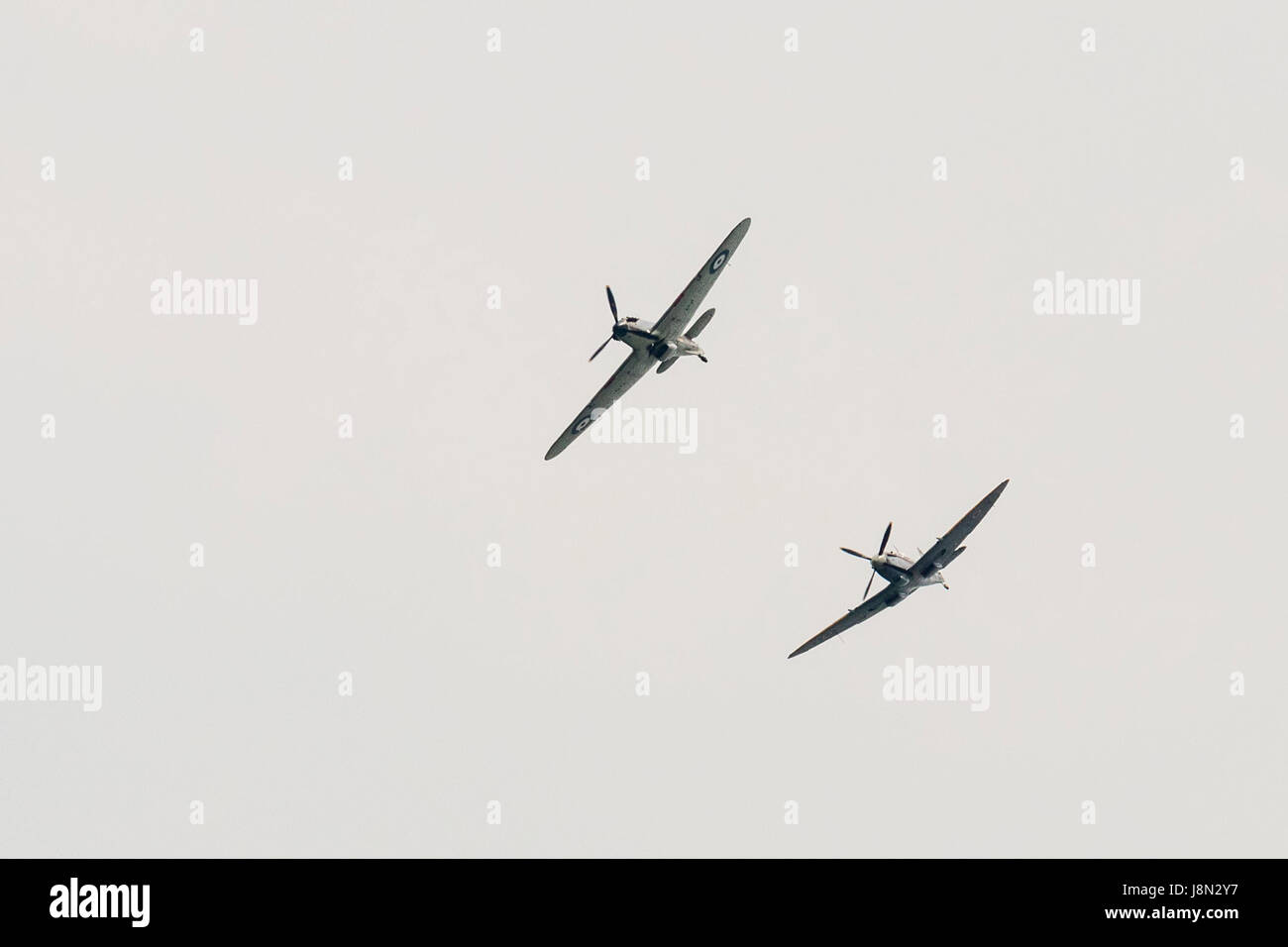 Vintage world war two Hawker Hurricane, followed by a spitfire, flying over head against a whitest sky. - Stock Image