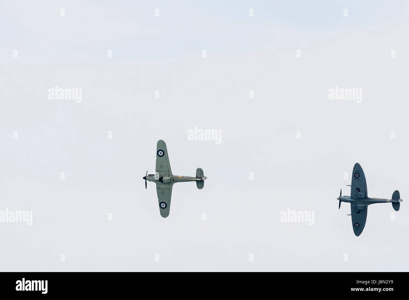 Vintage world war two Hawker Hurricane, followed by a spitfire, flying over head against a white sky. - Stock Image