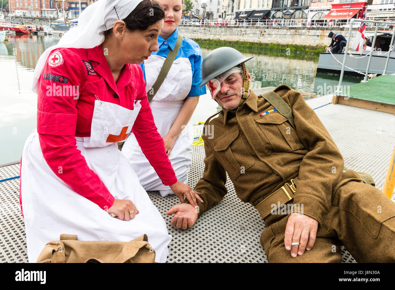 Dunkirk re-enactment at Ramsgate harbour, England. Red Cross nurse tending to wounded British soldier on deck of - Stock Image