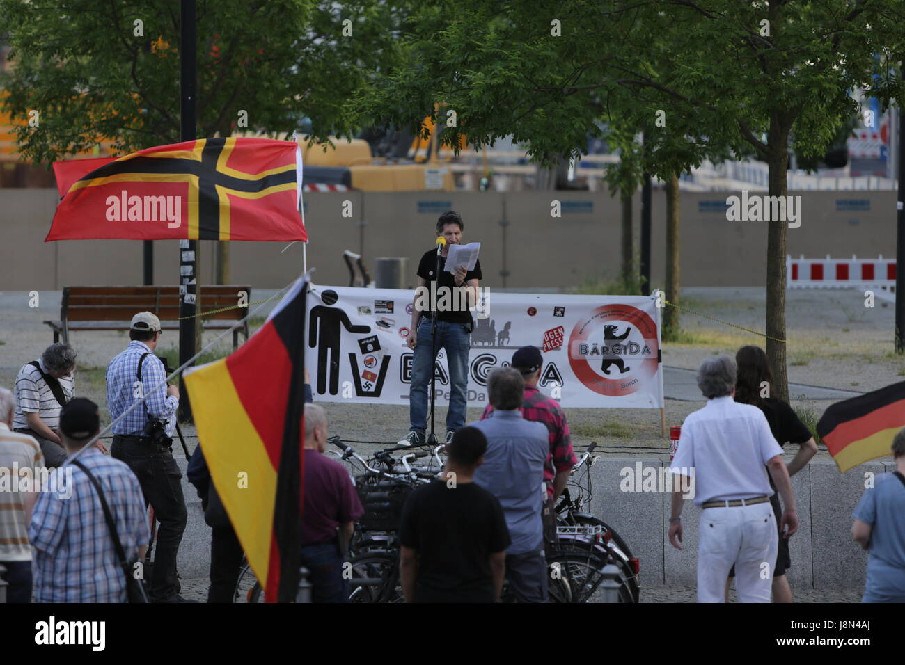 Protesters wave a Wirmer flag and a German flag, while another protester addresses the group. A handful of right - Stock Image