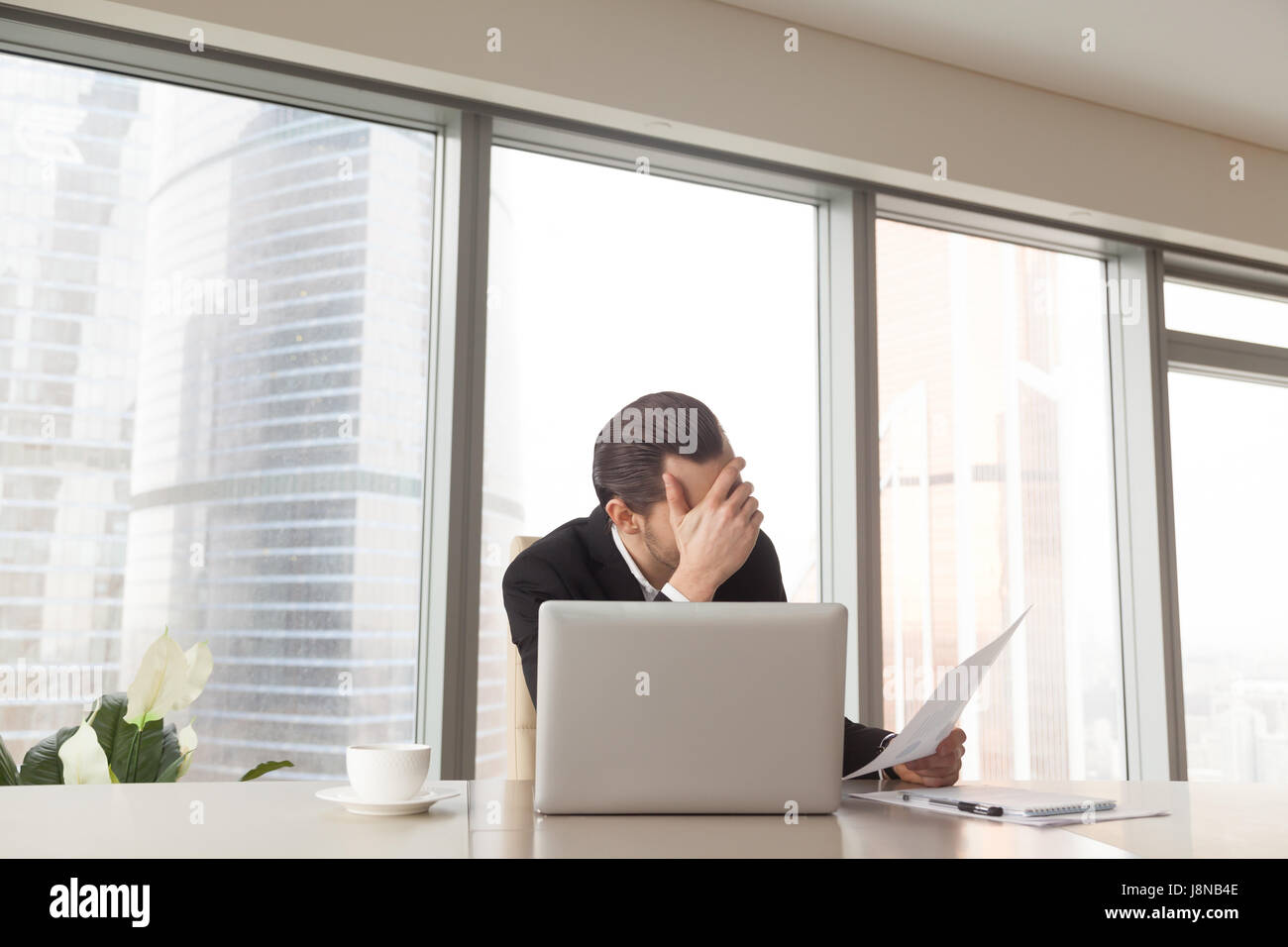 Sad entrepreneur sitting at office desk worries about bad financial results, head on hand. Fall in liquidity of - Stock Image