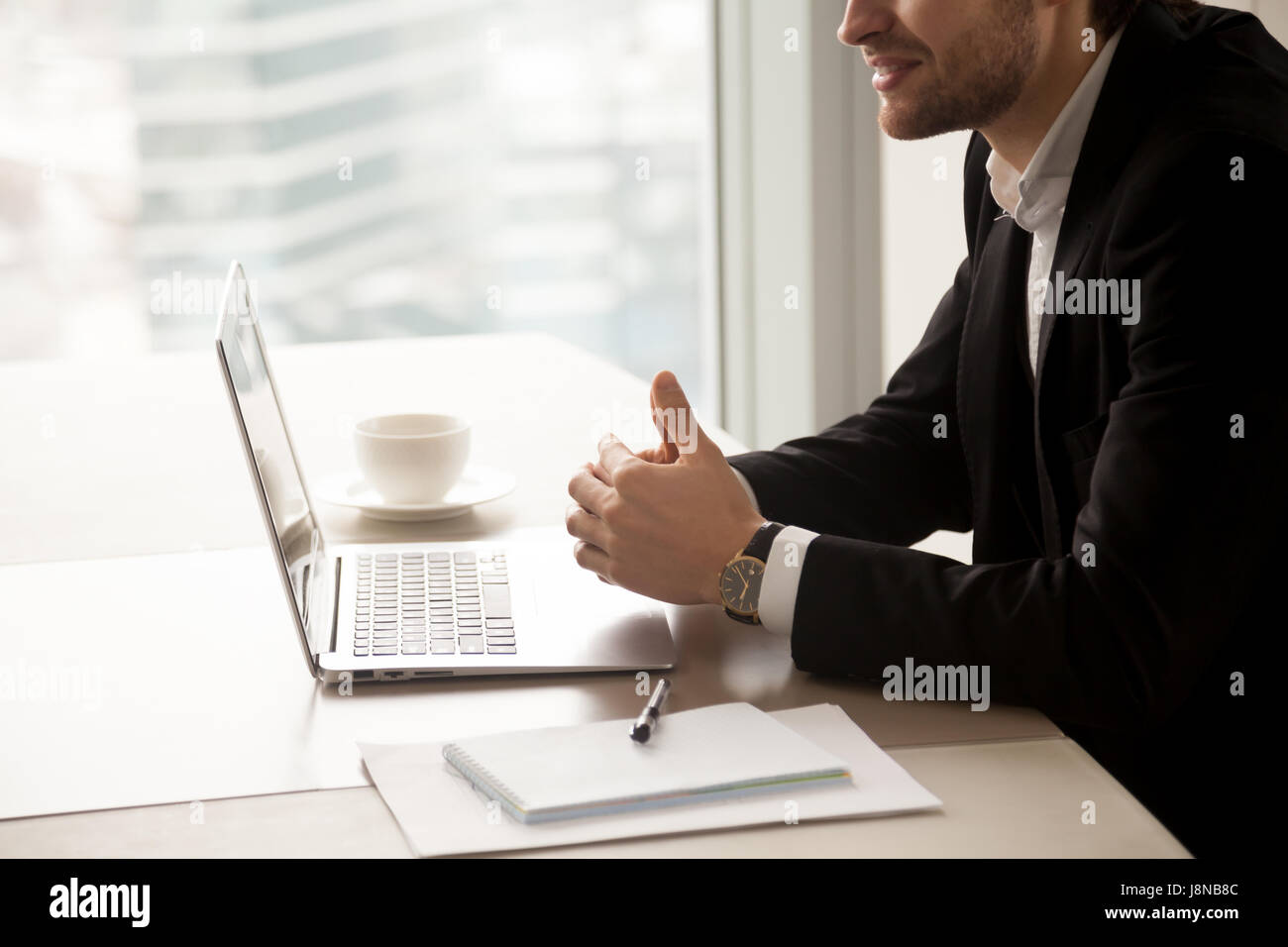 Close up photo of successful businessman sitting at desk with laptop and conducts negotiations. Male entrepreneur Stock Photo