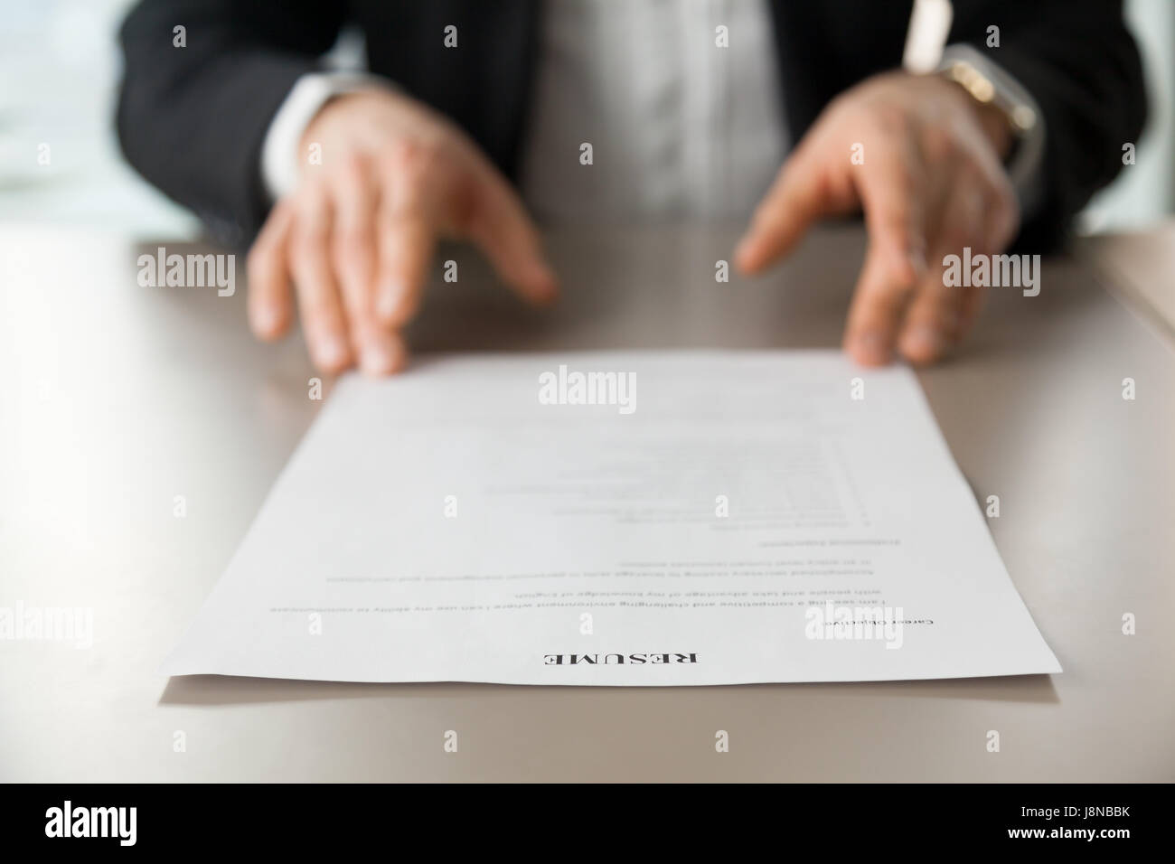 Resume document with guys hands in background. Recruitment manager reads resume. Job applicant offers CV to recruiter - Stock Image