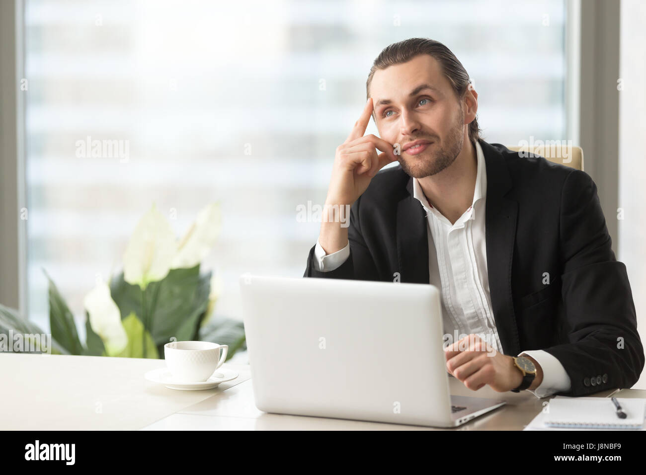 Young businessman dreaming about successful future at office desk. Attractive entrepreneur ponders decision, imagines - Stock Image