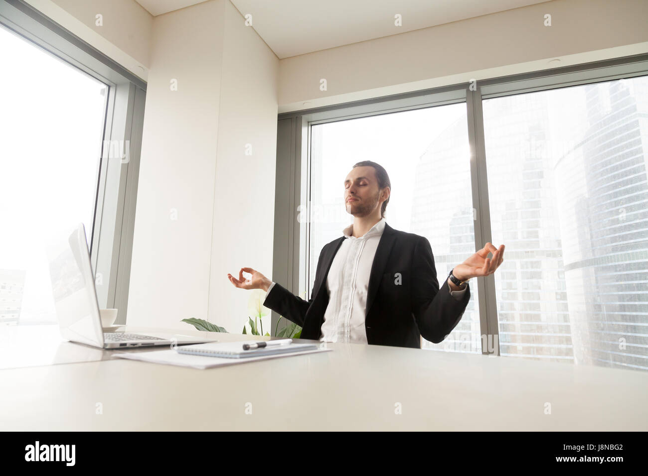 Young man meditating at laptop desk in office. Successful businessman doing yoga exercises at workplace for relaxing - Stock Image