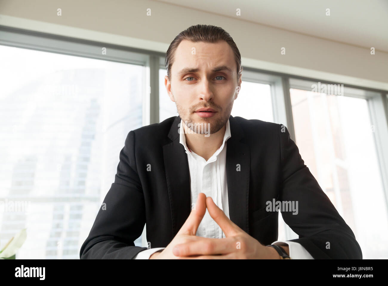 Businessman critically evaluates offers on meeting - Stock Image