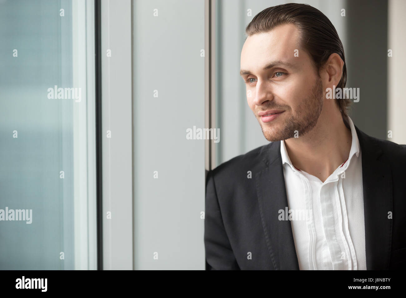 Successful businessman imagines great career - Stock Image