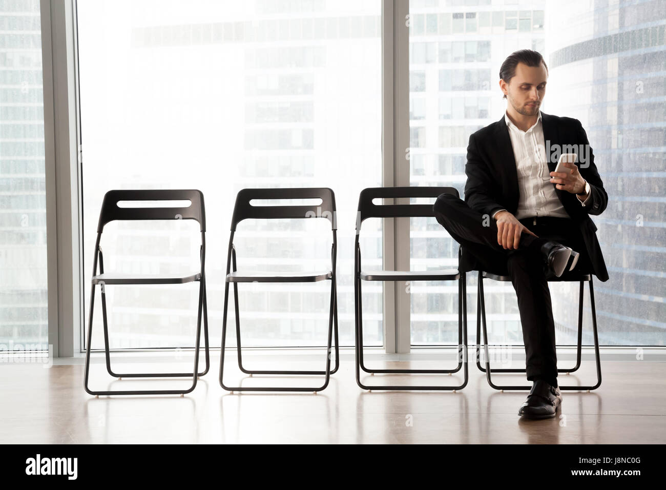Man with cellphone waiting his turn on interview - Stock Image