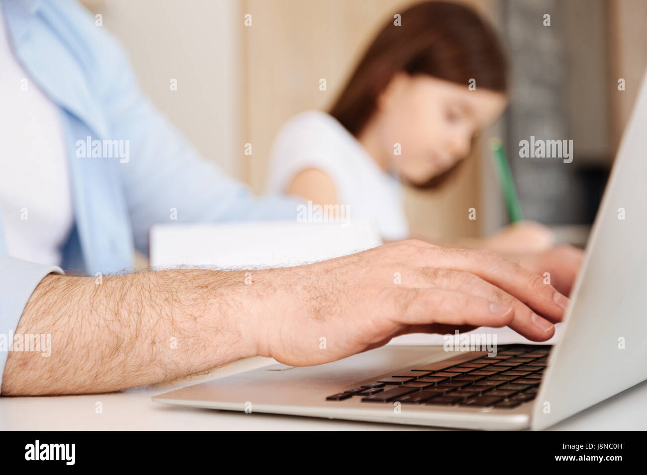 Hairy, well-groomed male hands typing on the laptop keyboard