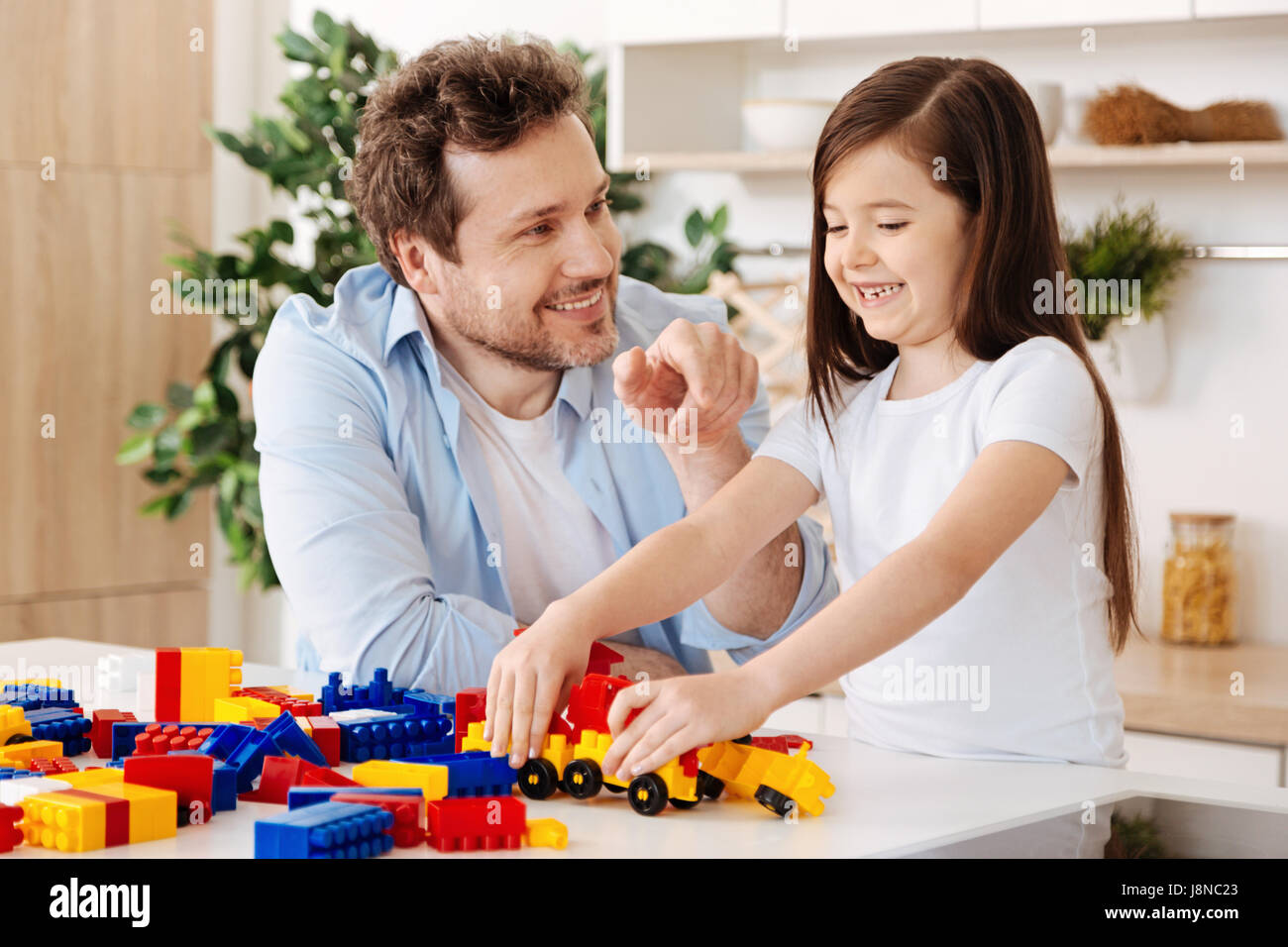 Sincere emotions. Pleasant cheerful father and his joyful little daughter looking happy and smiling broadly while Stock Photo